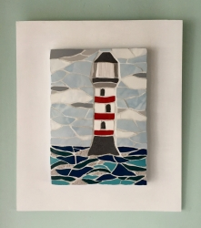 A large mosaic lighthouse with red detail, backed on a white board